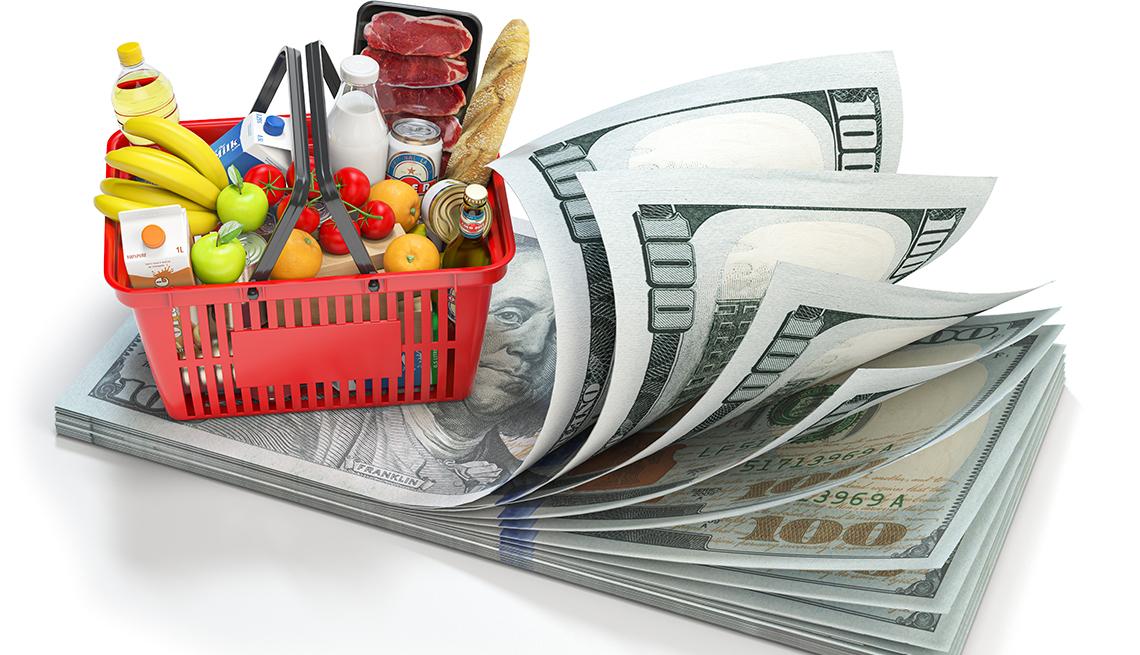 Canasta llena de frutas, verduras y embutidos sobre un fajo de billetes de 100 dólares