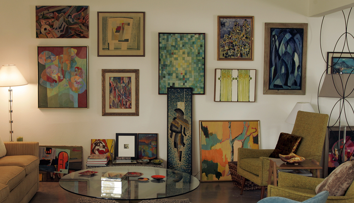 many colorful paintings hang on and lean against a wall in a living room
