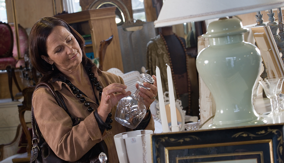 woman browsing home goods at an estate sale