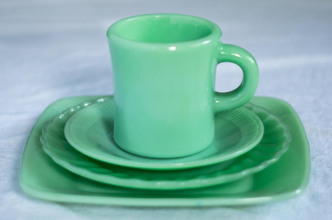 Taza de porcelana encima de varios platos pequeños