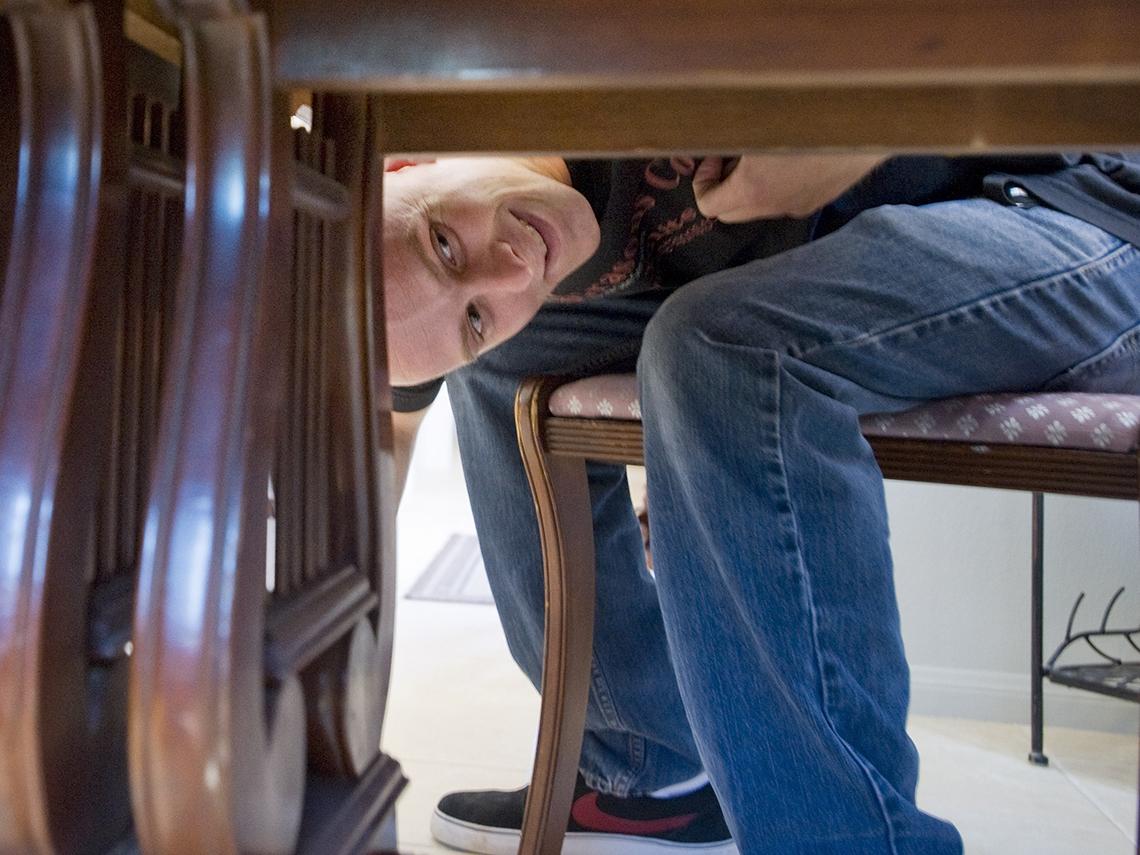 Hombre observa debajo de una mesa de madera