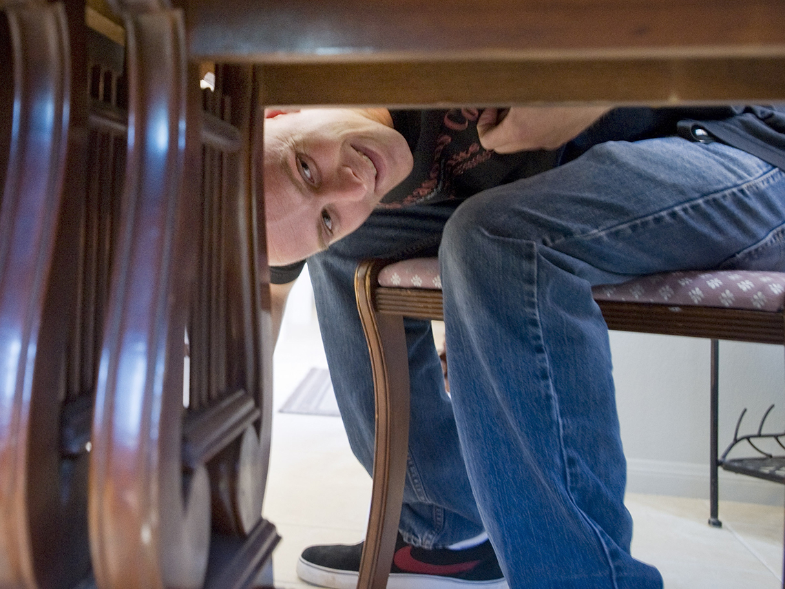 a man peeks under a dining room table to see if there is a label from the furniture maker