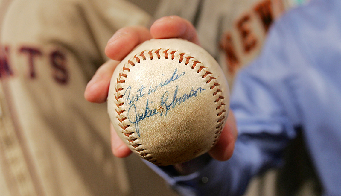 A baseball signed by Jackie Robinson is held up for view at a sports memorabilia auction