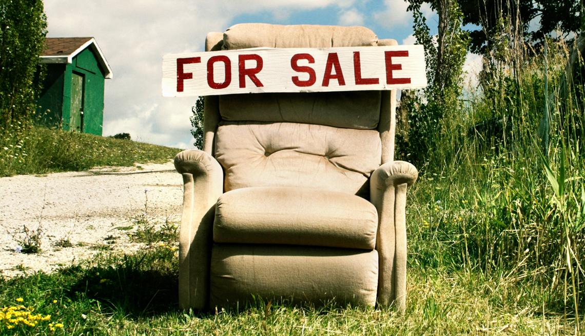 Una silla vieja en un patio con un letrero en inglés que dice se vende