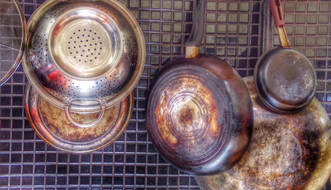 Vasijas viejas colgadas de una parrilla