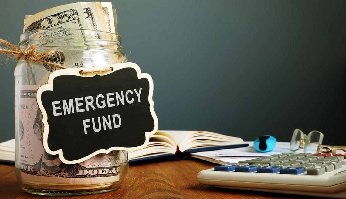 Jarra llena de dólares con un letrero que dice fondo de emergencias sobre una mesa