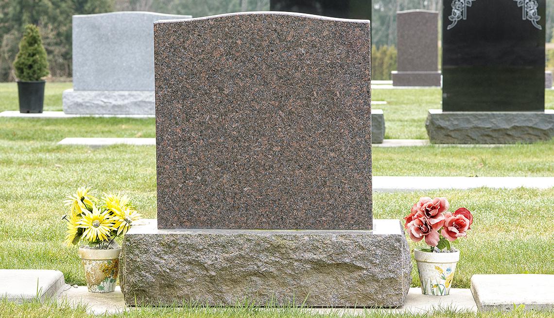 Lápida de un cementerio con flores alrededor