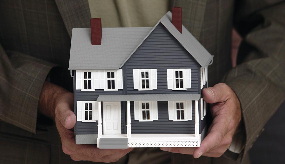 Manos de un hombre sosteniendo una maqueta y lo que deberías saber de las hipotecas revertidas