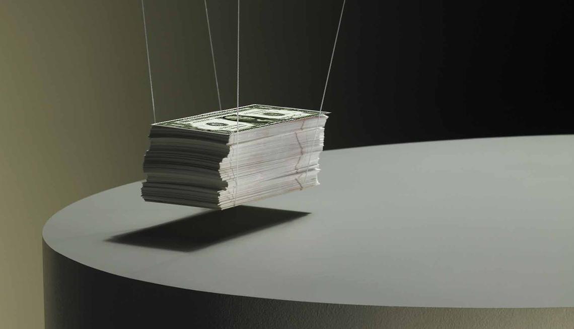 Fajo de dinero, sostenido por las esquinas con unas cadenas, y libérate de las deudas.