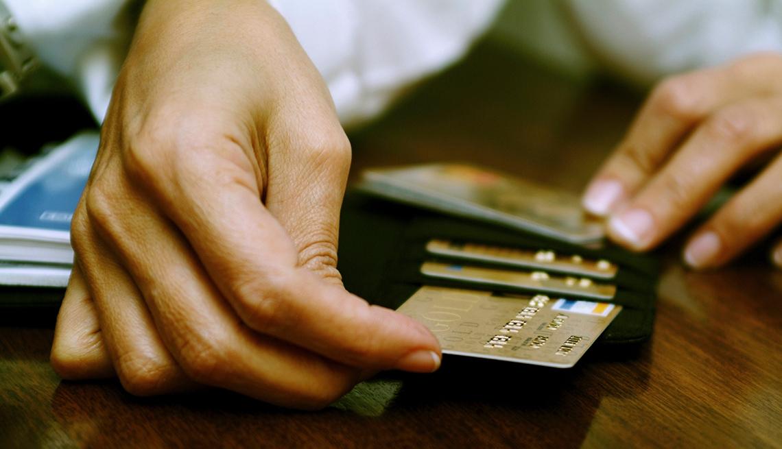 Manos sacando tarjetas de crédito de una billetera.