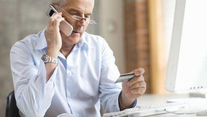 Un hombre llamando por teléfono a las compañias de tarjetas de crédito