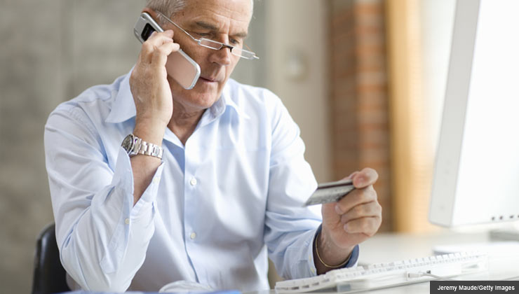 debt challenge negotiating with credit card companies mature man on phone with credit card
