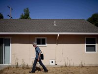 Man walking by house - with time one can rebuild one's credit score after a foreclosure.
