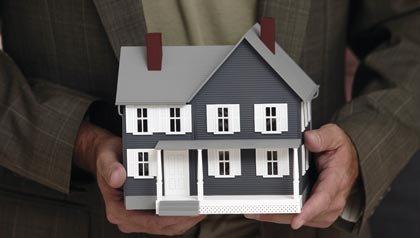 Un hombre sosteniendo una maqueta de una casa