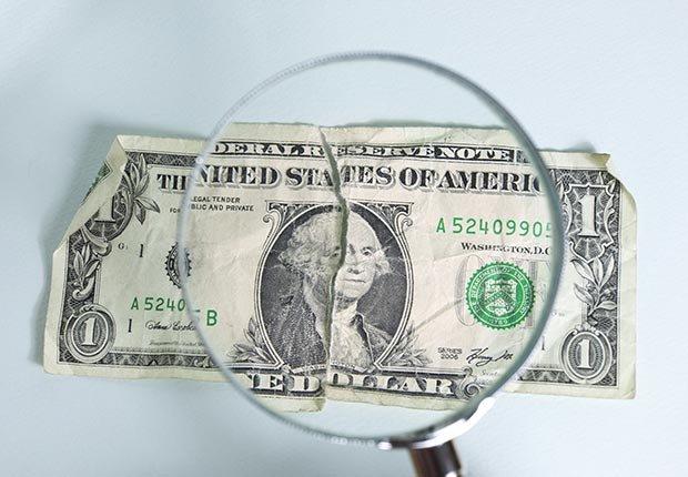 Billete de un dólar con una lupa