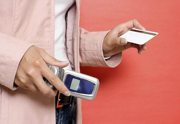 Mujer sosteniendo un teléfono y una tarjeta de crédito