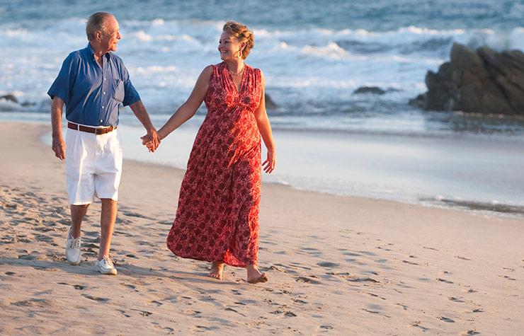 Pareja caminando por la playa - Cómo retirarme sin deudas