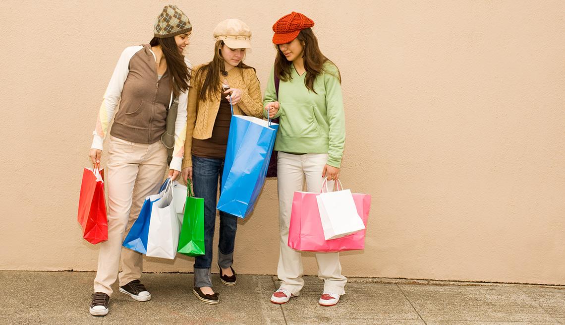 Mujeres jóvenes con bolsas de regalo - Errores en las compras navideñas con tarjetas de crédito