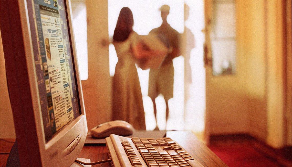 Computador en una casa y al fondo una mujer recibiendo un paquete de un cartero - Errores en las compras navideñas con tarjetas de crédito