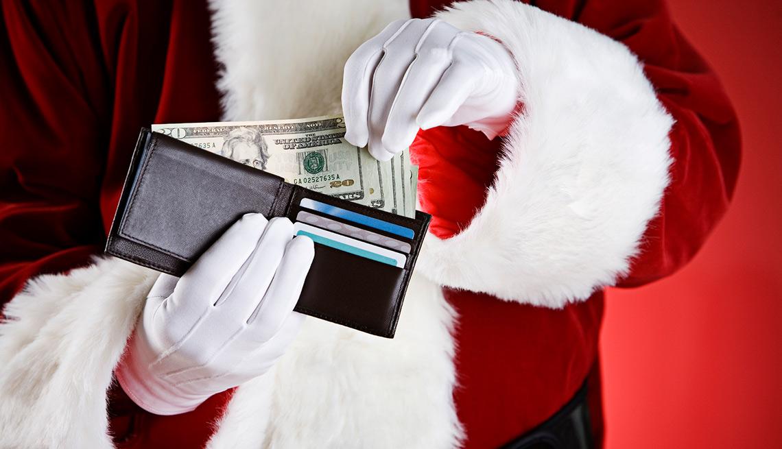 Billetera sostenida por manos de un hombre con traje de Papa Noel - Errores en las compras navideñas con tarjetas de crédito