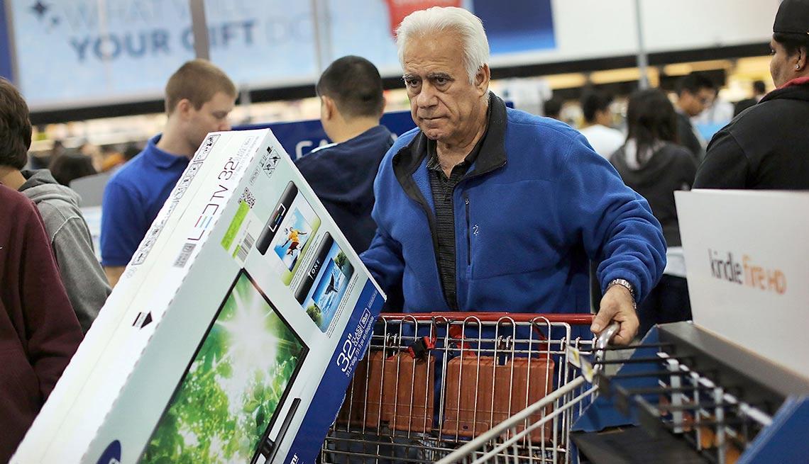 Hombre arrastrando un carro de compras al interior de una tienda de Best Buy - Devoluciones de las compras de navidad