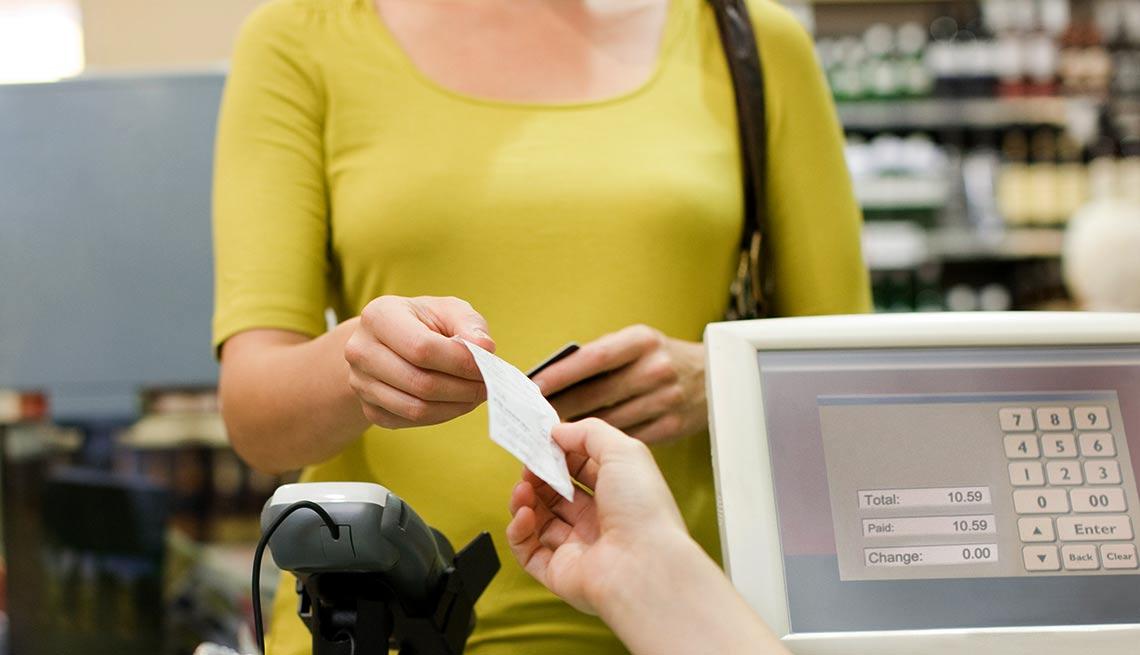 Mujer mostrando un recibo de compra a otra persona frente a una caja registradora - Devoluciones de las compras de navidad