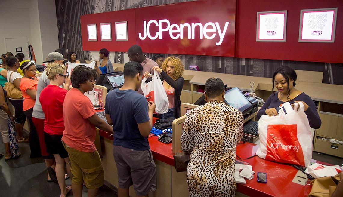 Personas frente a un mostrador de registradoras de una tienda de J.C. Penney - Devoluciones de las compras de navidad