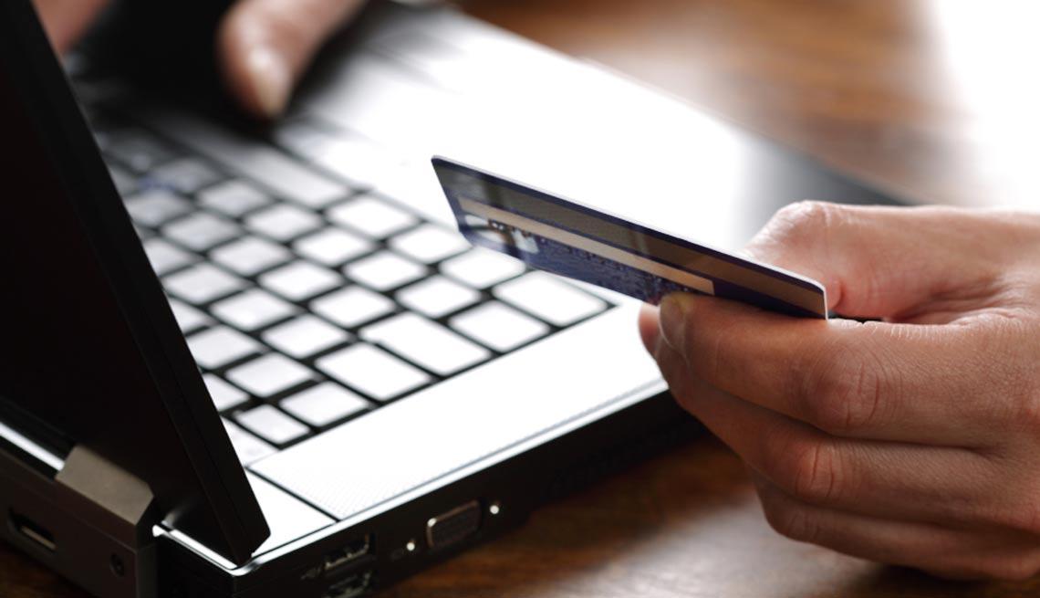 Manos de un hombre con una tarjeta de banco frente a una computadora portátil - Devoluciones de las compras de navidad