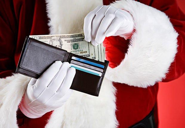 Billetera sostenida por manos de un hombre vestido de Papa Noel - Errores en las compras navideñas con tarjetas de crédito