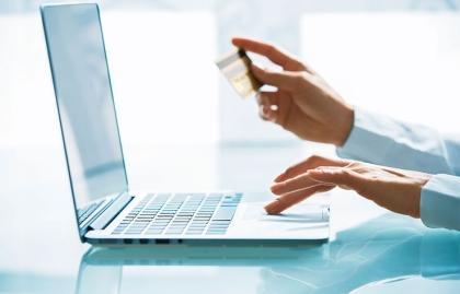Manos con una tarjeta de crédito frente a un computador - Opciones para eliminar las deudas de tu tarjeta