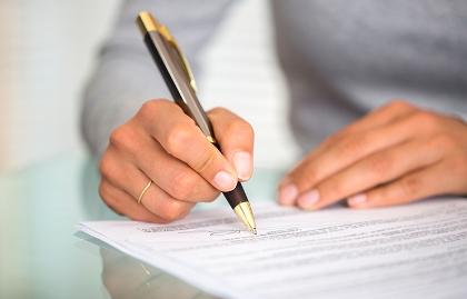 Manos de una mujer firmando un contrato... cuidado cuando eres codeudor de un préstamo