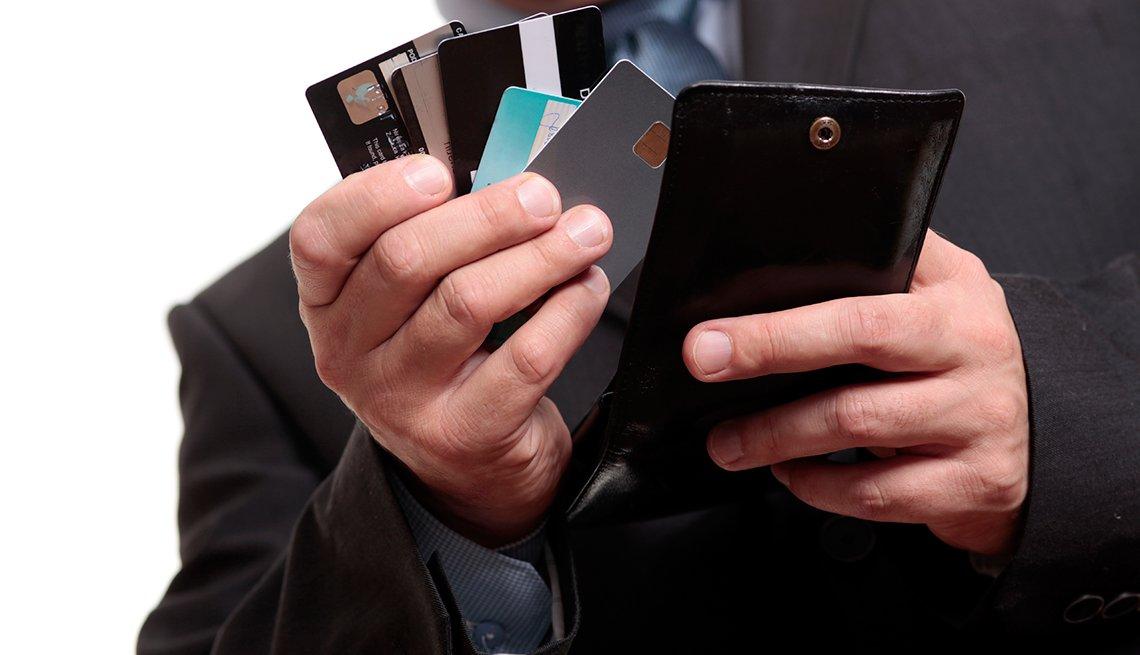 Manos de un hombre sosteniendo tarjetas de crédito sacadas de su billetera. Solo quédate con las mejores