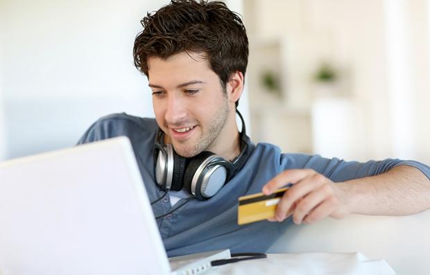 Hombre joven frente a una computadora portátil y con una tarjeta de crédito en la mano