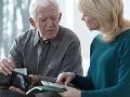 Hombre mayor sosteniendo dinero de su billetera en la mano y sentado al lado de una mujer que lo mira mientras sostiene una calculadora. Cuidado con el abuso financiero