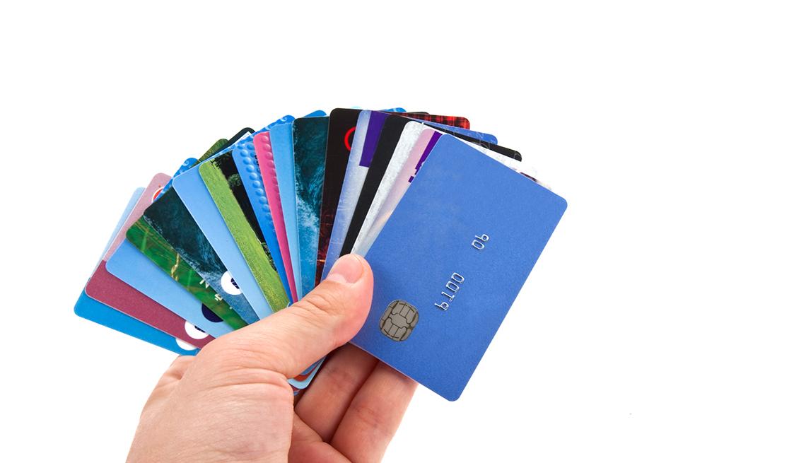 Mano izquierda sosteniendo varias tarjetas de crédito y cómo deberías manejarlo.