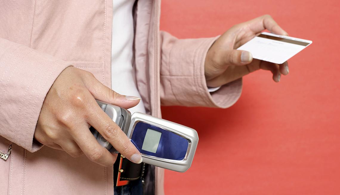 Hombre con un teléfono y una tarjeta en sus manos - Errores comunes con las tarjetas de crédito