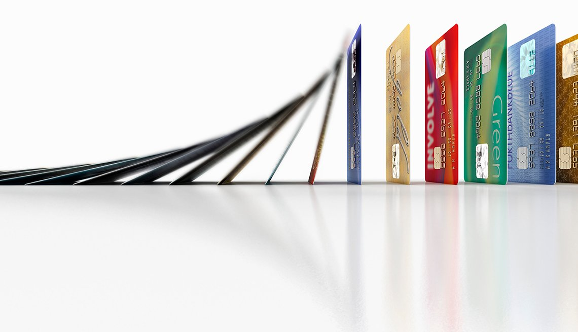 Fila de tarjetas de crédito cayendo como piezas de domino y aprende a mejorar tu puntaje crediticio