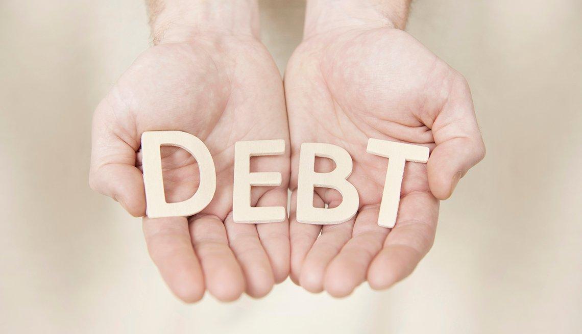 Manos sosteniendo la palabra Debt, que traduce deuda.