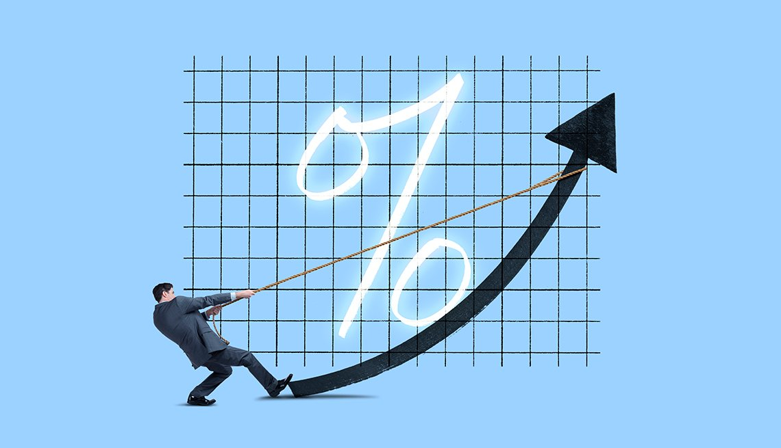 A businessman pulls on a rope attached to an arrow that represents rising interest rates