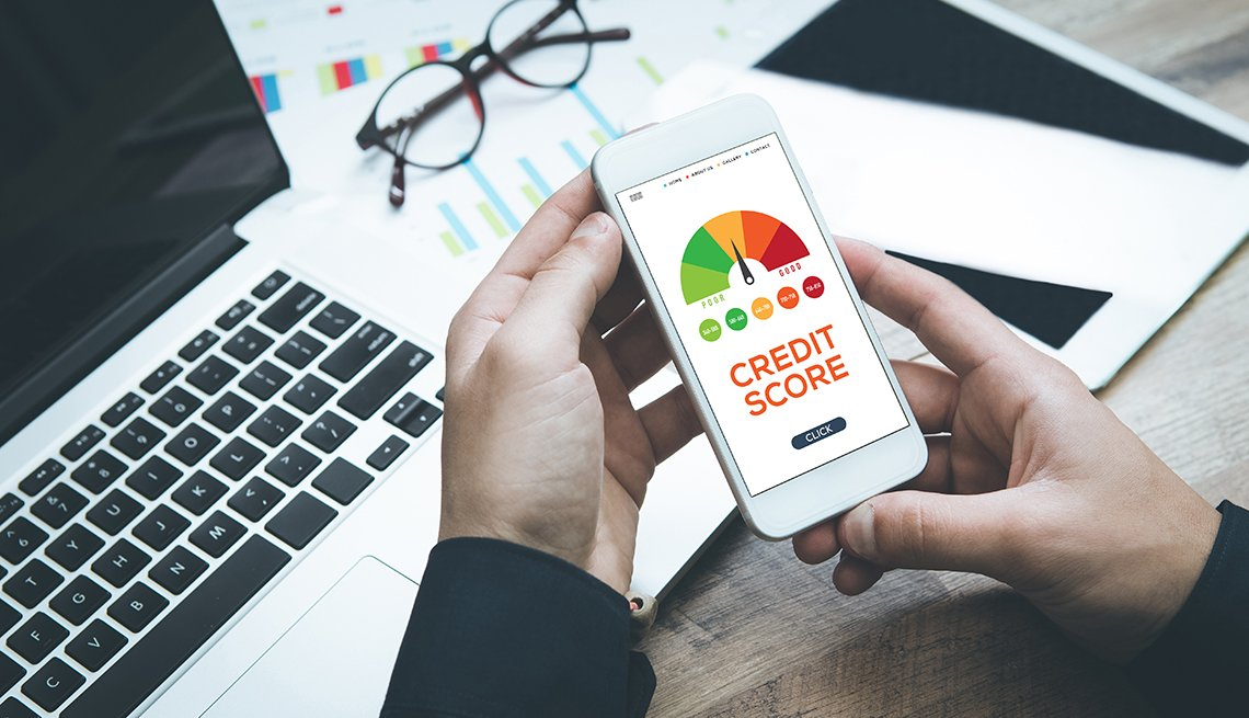 Person holding smartphone with image of credit score website on it
