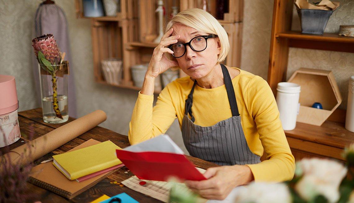 Mujer en una oficina con mano en la frente y un papel en la mano.