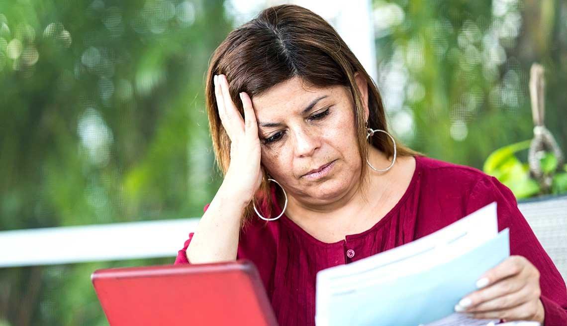 Mujer con documentos en la mano y una mano en la cabeza