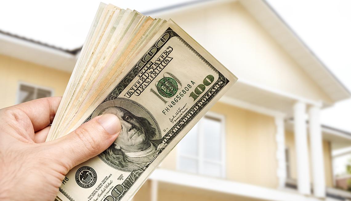 Mano sosteniendo un fajo de dólares en el exterior de una casa.