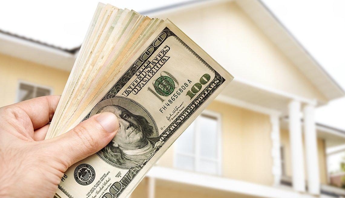 handful of cash held in front of exterior of home