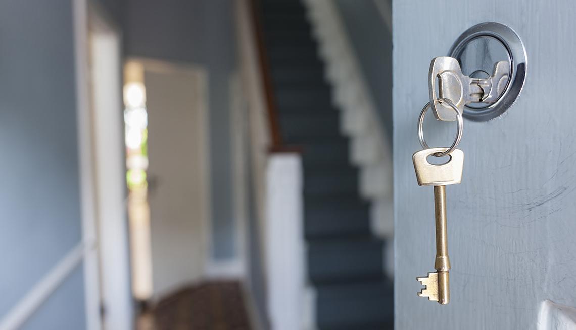 Frente de una casa con una puerta abierta con la llave en la chapa.