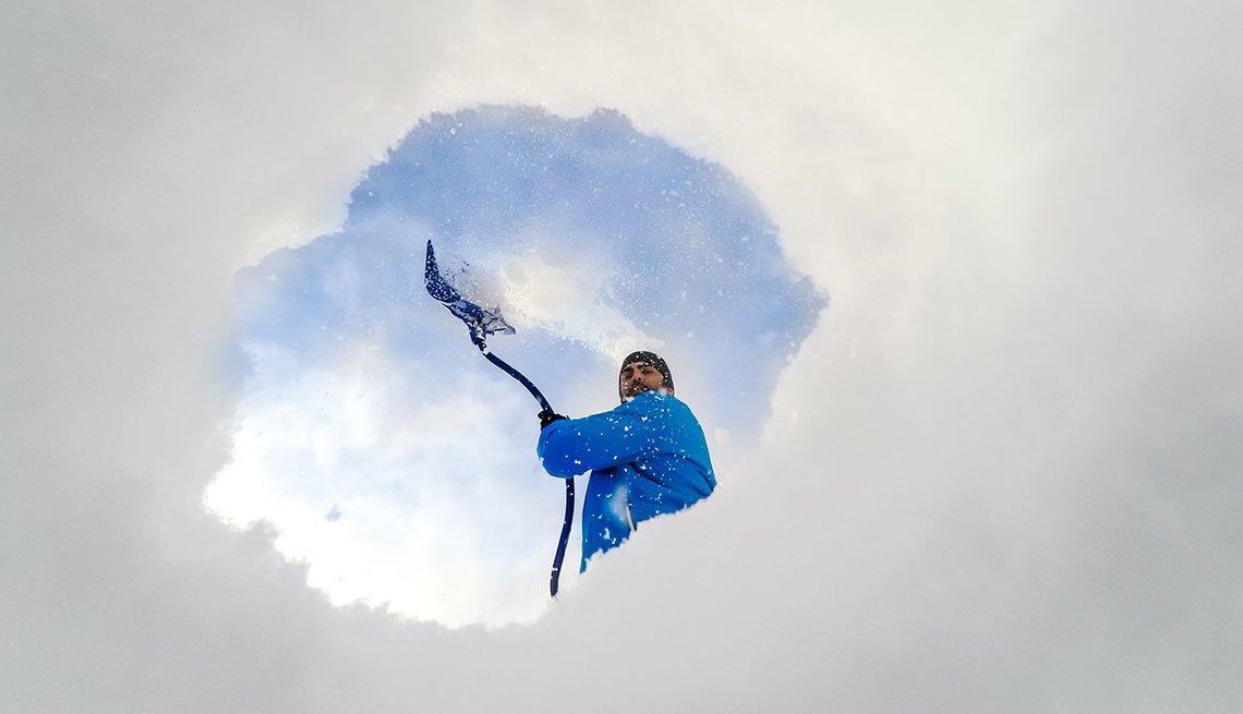 Vista desde la parte interior de un hueco en la nieve que deja ver un hombre con una pala.