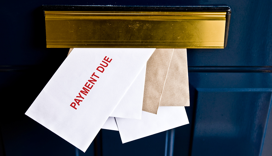 Letters in front door mail slot saying payment due