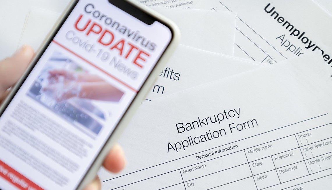 Teléfono móvil con una pantalla que muestra una actualización noticiosa del coronavirus y formularios de bancarrota y desempleo en el fondo.