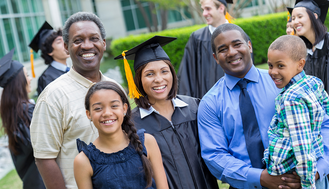 Happy mature man poses with his adult daughter after her college graduation. The graduate's husband and children are also in the photo.