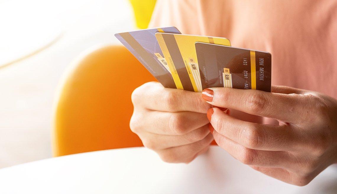 Manos de una mujer con varias tarjetas de crédito en la mano.